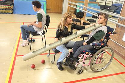 Menino em uma cadeira de rodas praticando bocha